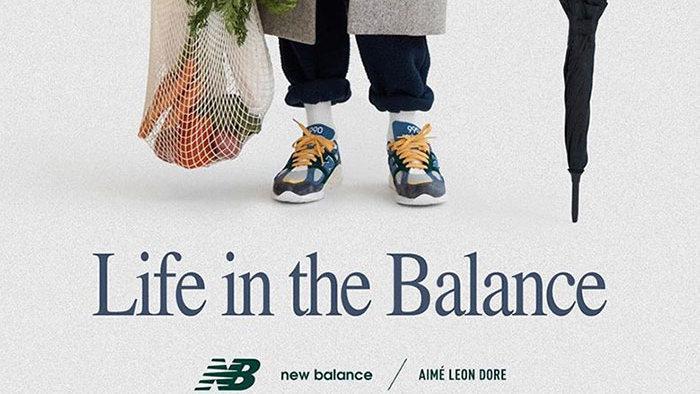 کفش های نیوبالانس در پا یک فرد میانسال با سبد خرید و چتر در دست از نمای زانو به پایین به همراه نوشته life in the balance در پایین تصویر